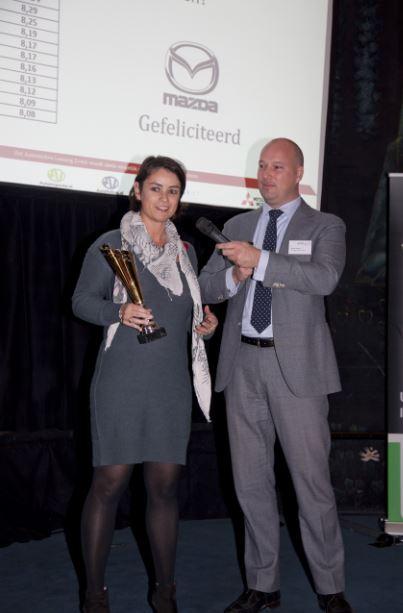 Geraldine Brouwers, Algemeen Directeur Mazda Motor Nederland, neemt de prijs in ontvangst van Martin Huisman van de VAVDZ